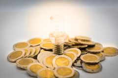 The Bulb Is Placed Stack Of Coins, The Bulb Is Lit In Darkness. Image Use For Finding A Way Out In The Dark Stock Photos