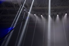 Free The Camera On The Operator`s Crane Flies Against The Background Of Bright Rays Of Searchlights. Stock Photos - 174205513