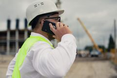 Free The Chief In A Jacket And A Construction Helmet With Smartphone In His Hands, Against The Background Of A Tower Crane And The Sky Stock Image - 194855131