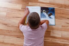 Free The Child Lies On His Stomach On The Floor And Reads A Big Book Royalty Free Stock Photo - 193298515