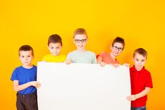 Free The Different Little Boys Are Holding A Big White Paper Royalty Free Stock Photos - 225280138