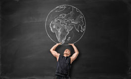Free The Earth Pictured On Blackboard And Sporty Man Acting Like He Is Holding It Up Above Himself Stock Images - 79063724