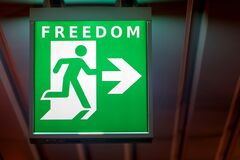 Free The Emergency Exit Sign Indicates The Direction Of Way To Freedom Stock Photography - 216886842