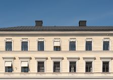 The Facade Of The City Building, Windows And Roof Against The Blue Sky Stock Photo
