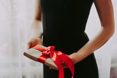 Free The Girl Is Holding A Gift With A Red Ribbon. A Woman In A Black Dress On A White Background Is Holding A Box With Red Royalty Free Stock Images - 136519549