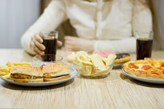Free The Girl Is Sitting At The Table And Eating Fast Food. Stock Image - 90065181