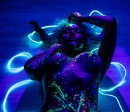 The Girl Is The Image Of The Devil, Contact Lenses And With Horns. Woman In UV Paint. Fluorescent Powder. Body Art Stock Images