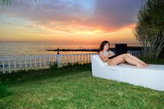 Free The Girl Lay On A Plank Bed With The Laptop At Sunset Stock Image - 159781661