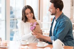 The Guy Gives Flowers To The Girl In The Cafe. Royalty Free Stock Photos