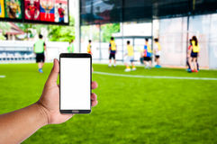 Free The Hand Of Man Hold Mobile Phone Over Blurred Athlete Are Playing Footbal Or Soccerl On Artificial Yard Royalty Free Stock Photography - 74630297