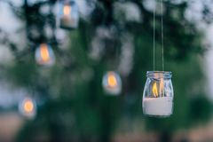 Free The Lamp Made Of A Jar With A Candle Is Hanging On A Tree At Night. Wedding Night Decor Royalty Free Stock Photos - 141025698