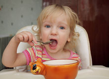 The Little Girl She Eats With A Spoon Stock Photo