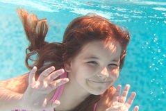 The Little Girl Swimming Underwater And Smiling Stock Photography