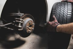 Free The Mechanic`s Hand Holding Black Tires For Changing Alloy Wheel Stock Images - 186546714
