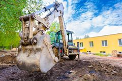 Free The Modern Excavator Performs Excavation Work On The Construction Site. Front View Of A Digger Bucket Of Digging Ground Royalty Free Stock Images - 125860329
