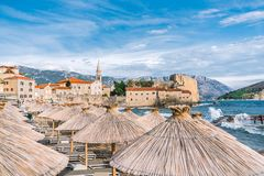The Old Town Of Budva. The Beach Of Budva. Umbrellas On The Beach In The Foreground. Clear Sunny Day, Blue Sky Over The Stock Image