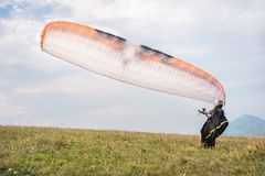 Free The Paraglider Opens His Parachute Before Taking Off From The Mountain In The North Caucasus. Filling The Parachute Wing Stock Image - 123842271