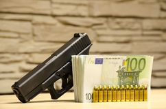 The Pistol With Bullets Stays Behind Money With Bllured Wall Backspace. Royalty Free Stock Photo