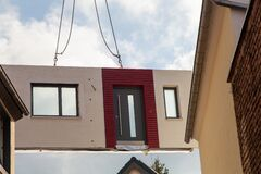 Free The Prefabricated Part For A Prefabricated House With Windows And A Red Bordered Front Door Is Picked Up By The Truck Crane And Li Stock Images - 188608334