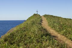 Free The Road Leading To The Top Of The Hill Near The Cliff On The Seashore, On Which Is Building An Old Wooden Cross Stock Photos - 179958683