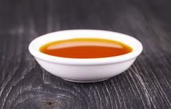 Free The Sea Buckthorn Oil In The White Small Cup On Old Wooden Background Stock Photography - 154549772
