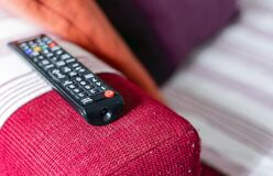 Free The Television Remote Control On The Armrest Of A Red Fabric Sofa Stock Photos - 201812543