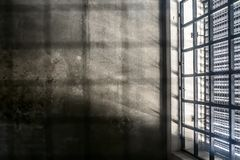 The Very Sober Interior Of A Prison Cell: Barred Windows With Little Light Coming In And Bare Concrete Walls Stock Photos