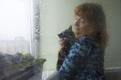The Woman And Her Cat Through Wet Glass Rainy Day Royalty Free Stock Photography