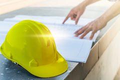 Free The Yellow Safety Helmet With The Man Verify Blueprint For His Project Royalty Free Stock Image - 147124436