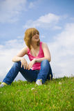 The Young Girl Sitting On A Green Grass Royalty Free Stock Photo