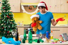 The Young Man Cleaning Kitchen After Christmas Party Royalty Free Stock Photography
