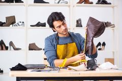 The Young Man Repairing Shoes In Workshop Stock Image