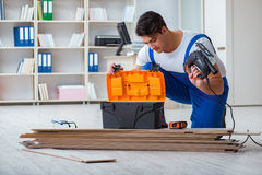 The Young Worker Working On Floor Laminate Tiles Stock Photo