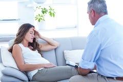 Thearapist advising pregenat woman on sofa Royalty Free Stock Photo