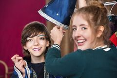 Theater assistant helps student dress as wizard. Theater assistant helps student dress for part as wizard in dressing room Stock Photography