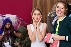 Theater assistant laughs as actress pouts at camera. Theater assistant laughs as the young actress pouts at the camera Stock Photo