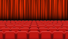 Theater auditorium with rows of red seats and stage with curtain Stock Photography