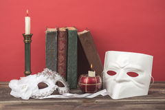 Theater concept. Closeup of white classical carnival masks with vintage books, burning candles in candlesticks on red background Royalty Free Stock Images