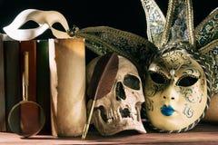 Theater en dramaconcept Menselijke schedel, Venetiaanse maskers met oude rol, boeken, vergrootglas en schacht op houten lijst Royalty-vrije Stock Afbeeldingen