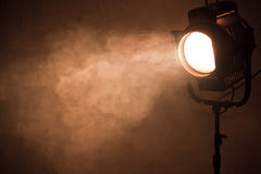 Theater spot light with smoke against grunge wall Stock Photo