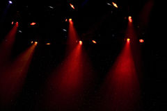 Theater spot lights on stage. A dark view of spot lights shining on a stage stock images