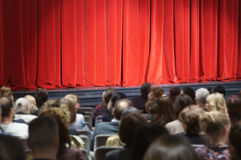 Theater stage. People sitting in front of theater stage covered with red curtain royalty free stock photos