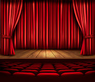 A theater stage with a red curtain, seats and a spotlight. Vecto Stock Image