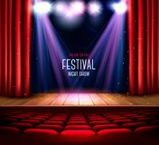 A theater stage with a red curtain and a spotlight. Stock Images