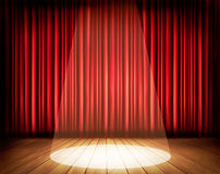 A theater stage with a red curtain and a spotlight. Stock Photos