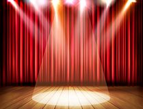 A theater stage with a red curtain and a spotlight Royalty Free Stock Photo