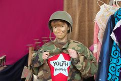 Theater student dressed as soldier. Student dressed as soldier holds jacket open and smiles at camera Stock Photography
