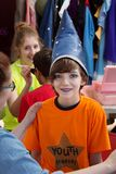 Theater Student in Wizard Hat. Theater teacher helps boy in orange shirt prepare for his part as a wizard Stock Photos