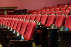 Theaterzaal voor bezoekers met mooie stoelen van Bourgondië-Rode fluweelstoelen vóór de show stock afbeeldingen