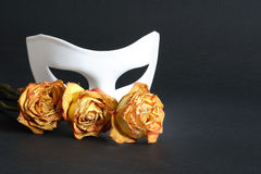 Theatre Concept On Black. White venetian mask and dry yellow roses on black background
